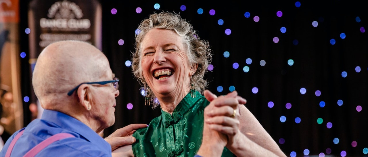 Two people dancing holding hands and other hand on woman's shoulder.  Man is on left, bald with glasses wearing a blue shirt with pink braces.  The woman is middle aged with curly short slightly grey hair, laughing.  In the background are coloured dots