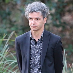 Image of a man with longish, greying hair and light skin wearing a blue jacket and a blue shirt standing outside during the day with long grass behind him.