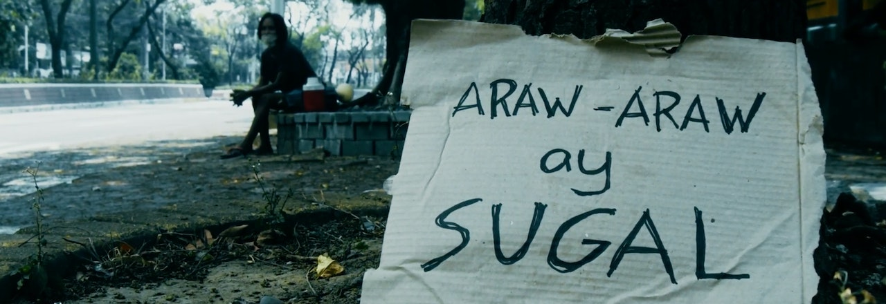 "Photograph of a sign saying ""Araw-Araw ay Sugal"".  In background is person sitting under a tree with a bag of things beside them.  In a park with other trees in background"
