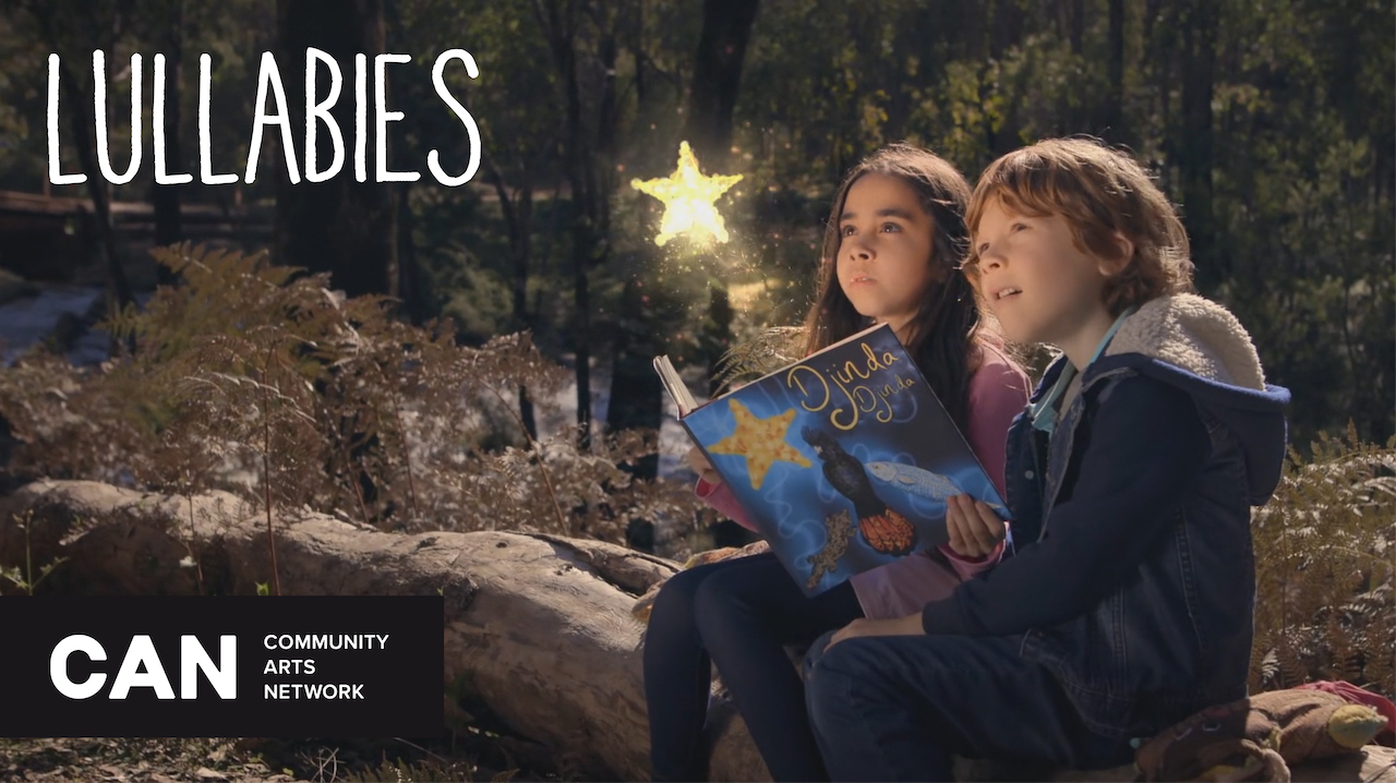 "Two young children looking up.  They are sitting on a log in the bush reading a book called ""Djinda"".  They are looking at a star that appears to be coming out of the book.  Words on left side say Lullabies and C.A.N. Community Arts Network"