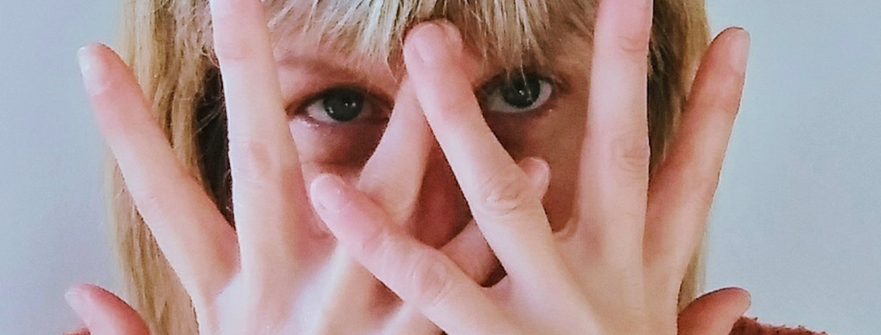 Woman's face hidden behind her fingers of both hands held in front.  Woman has straight blonde hair.