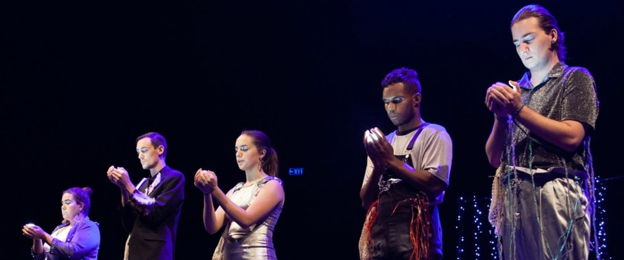 Photo taken at a performance on stage with stage lighting.  Five young people standing on a stage with their two hands cupped in front of their chest, staring into their hands. Some  small li