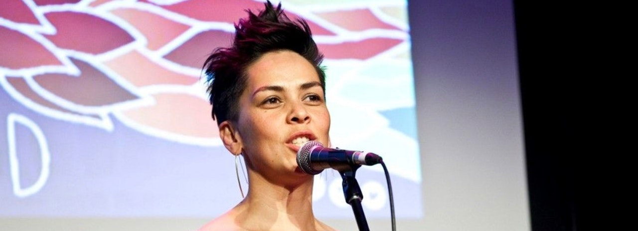 Photograph of woman on stage, from her shoulders up, talking into microphone.  Image of leaves projected onto background