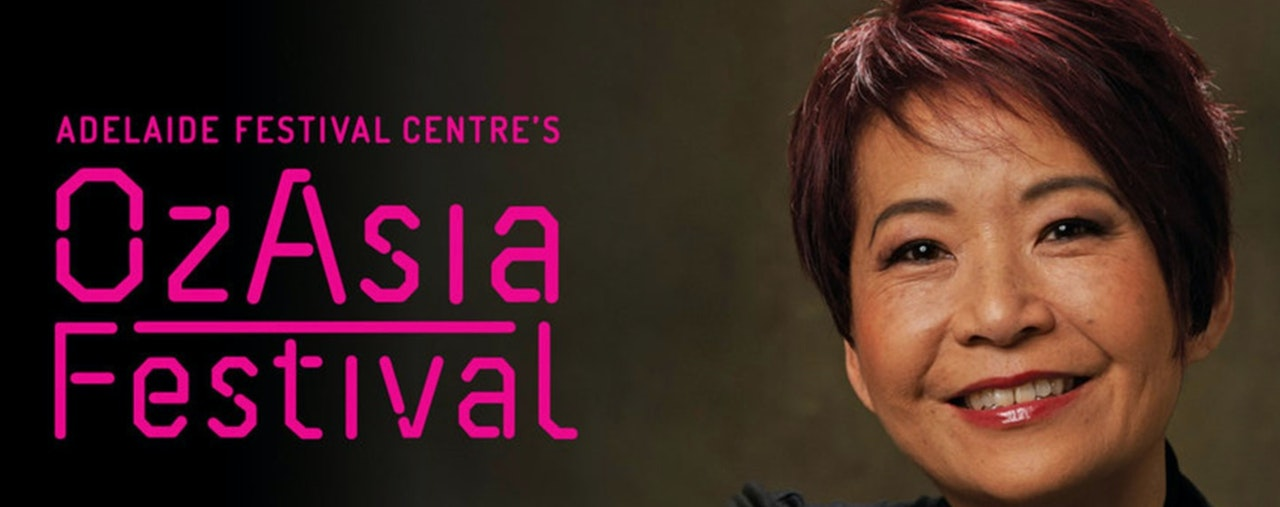 Close of woman's face on the right side of image.  Short cropped brown hair and  smiling.  Words say  Adelaide Festival Centre's OzAsia Festival