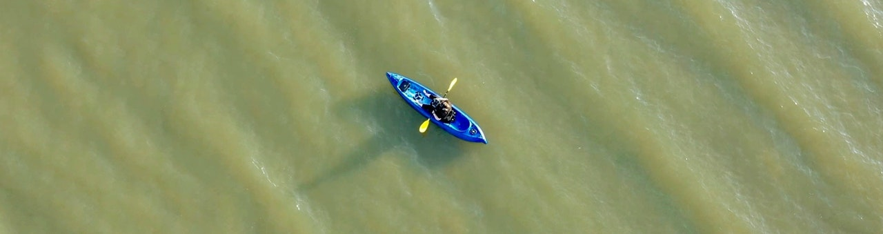 Overhead outdoor photograph, looking down on small canoe with one person in it and paddle leaning on the edge.  Floating on water with small waves
