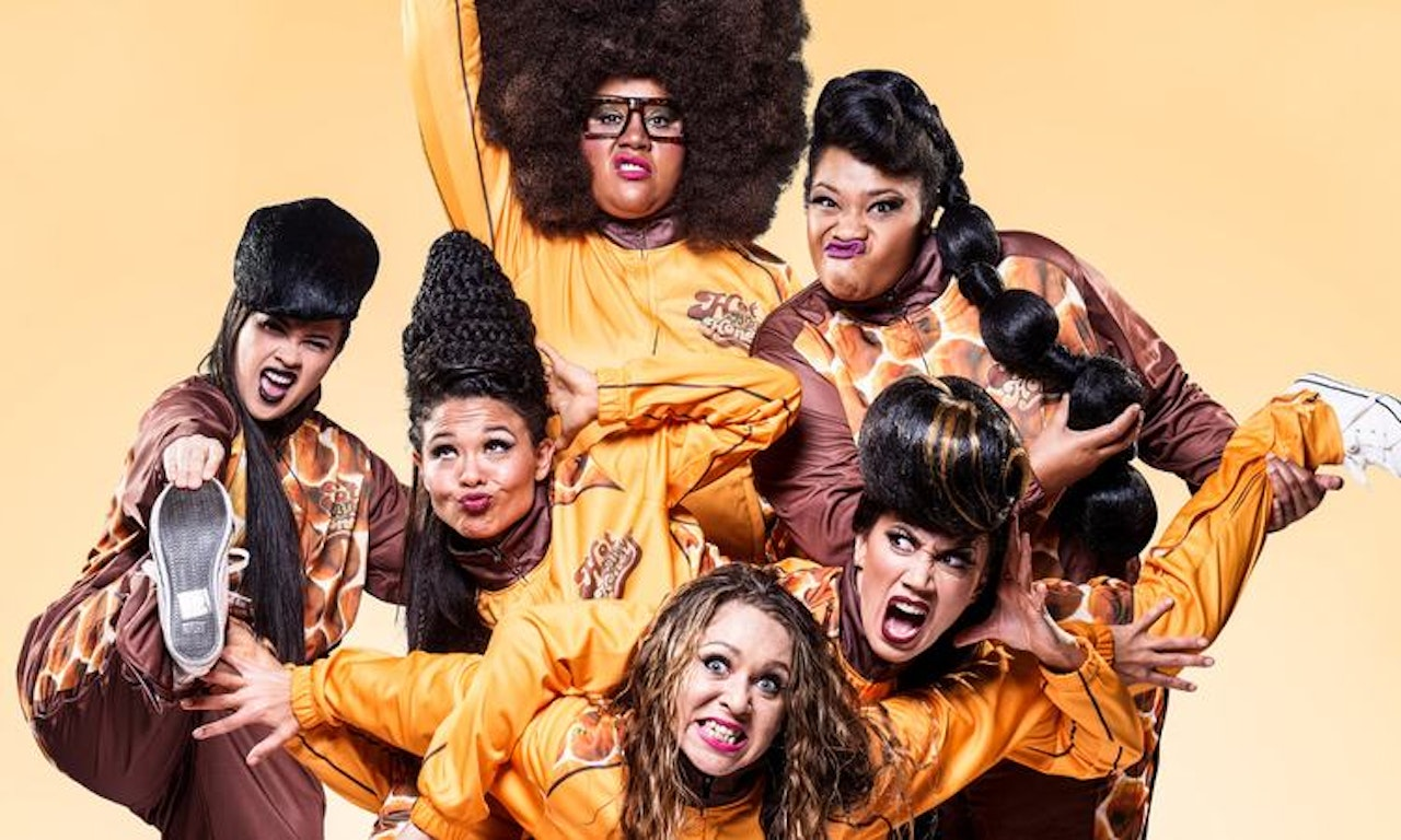 Photograph of performance group, Hot Brown Honey. Six woman of colour with costumes on doing strange poses with a leg in the air or holding someone.  Some are wearing wigs and one has eye gla