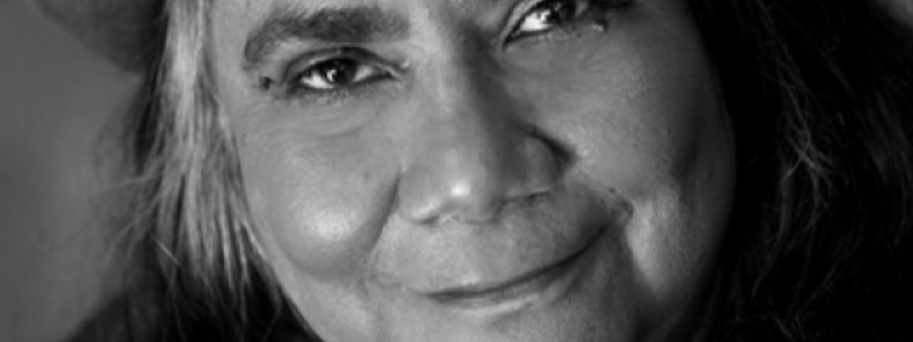 Photograph of Aboriginal woman, close up on her smiling.  Can see mouth, nose and eyes and some hair