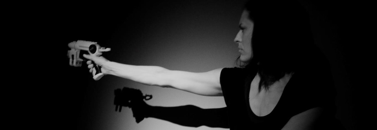 Photograph of a woman with long hair, standing in shadows holding a speed camera that looks like a gun. Image is in black and white