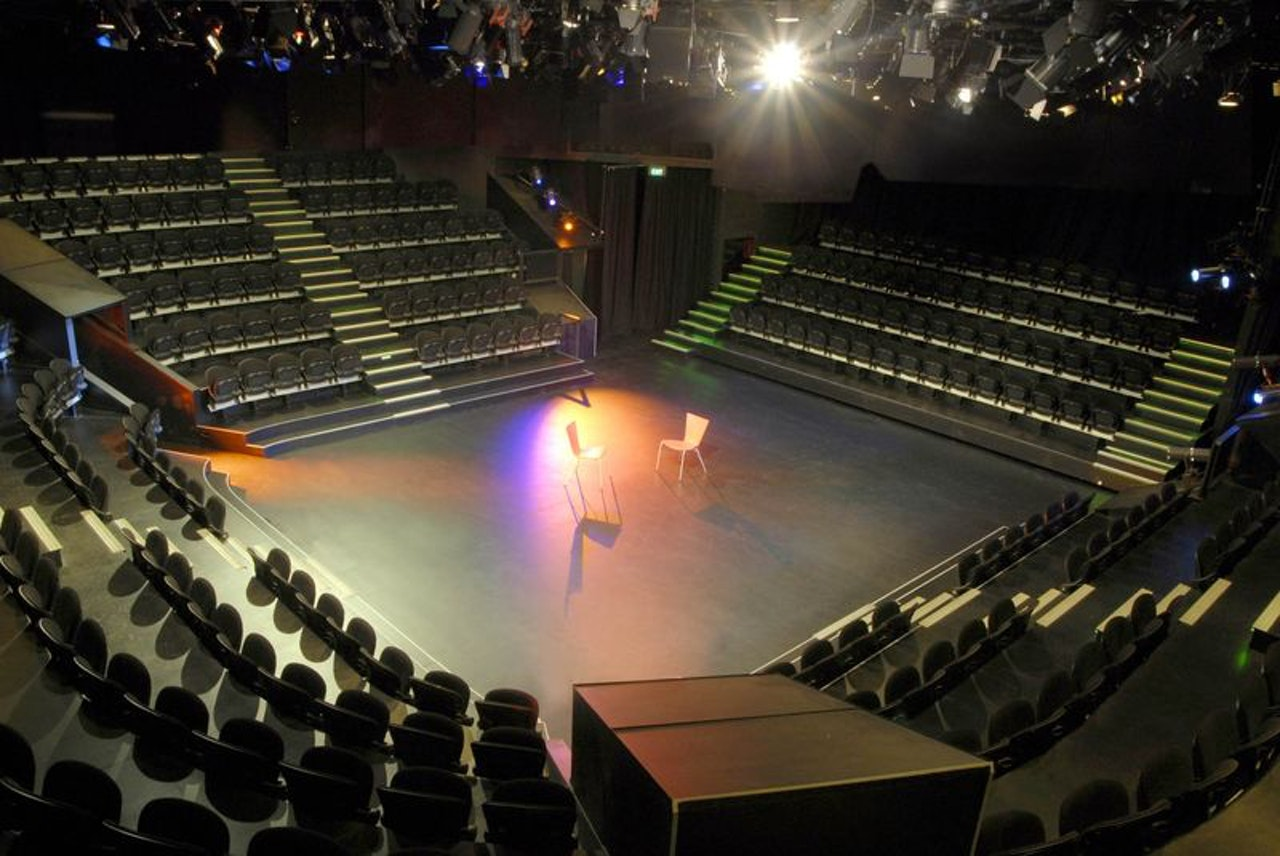 Inside a venue with theatre-in-the-round stage in the centre and rows of seats around it.  Stage lighting in the roof and two chairs in the centre of the floor.