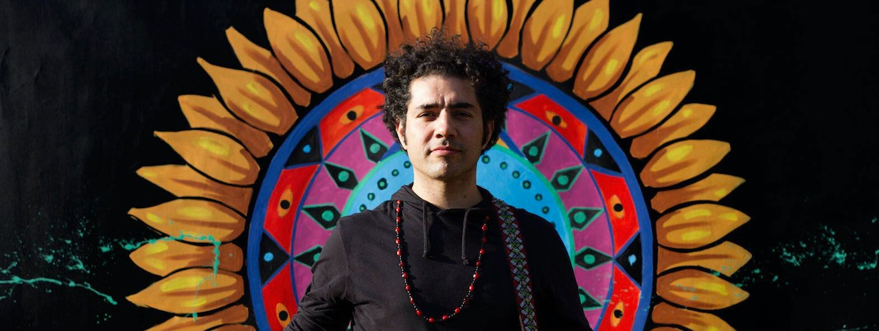 A young man with black curly hair wearing black and long red beads.  Standing in front of a painted mural of a flower with yellow petals.