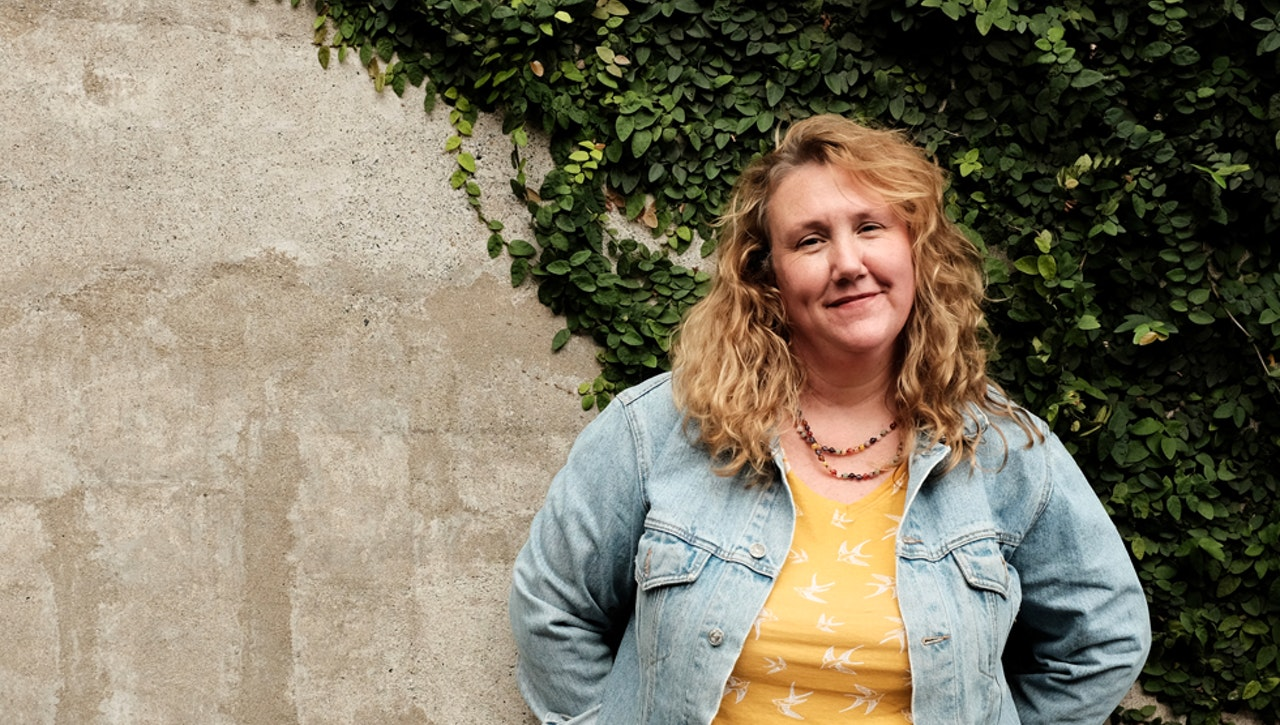 A woman standing in front of concrete wall with ivy plant covering half wall.  Woman is smiling, has light blonde hair that is curly and shoulder length.  Wearing a denim jacket and yellow t-shirt with bead necklace.