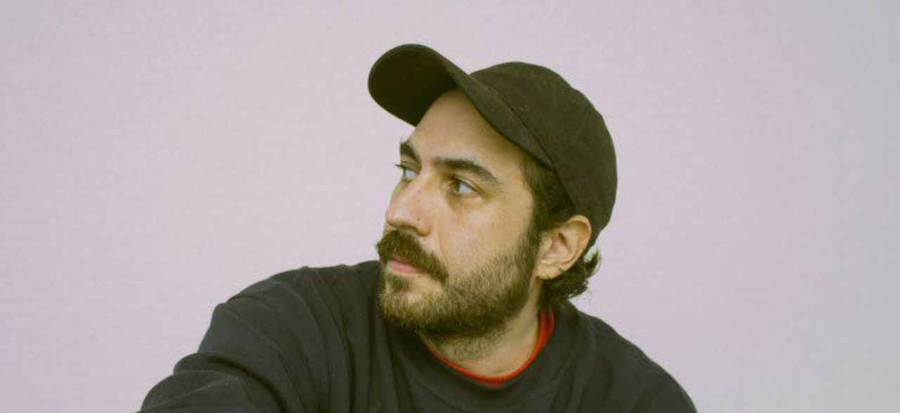 Photo of young man with a beard and wearing a cap and jumper.  Looking off to the side with no face expression