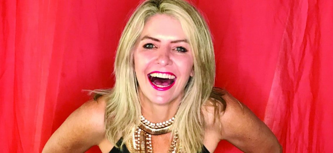 Photograph of a woman with large smile and happy, long blonde hair and wearing a sleeveless dress with chain straps..  With red backdrop