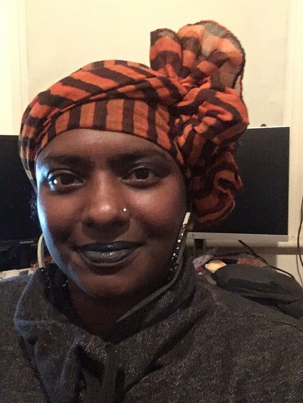 Photo attached description; woman smiling at the camera.  She has brown skin, wears a dark top and large hoop earrings; and an orange striped scarf is wrapped around her head.