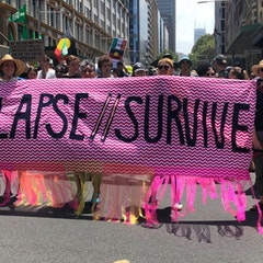 """Crowd of people, men and women on a city street.  Standing behind a pink banner with black text saying """"Collapse//Survive"""""""
