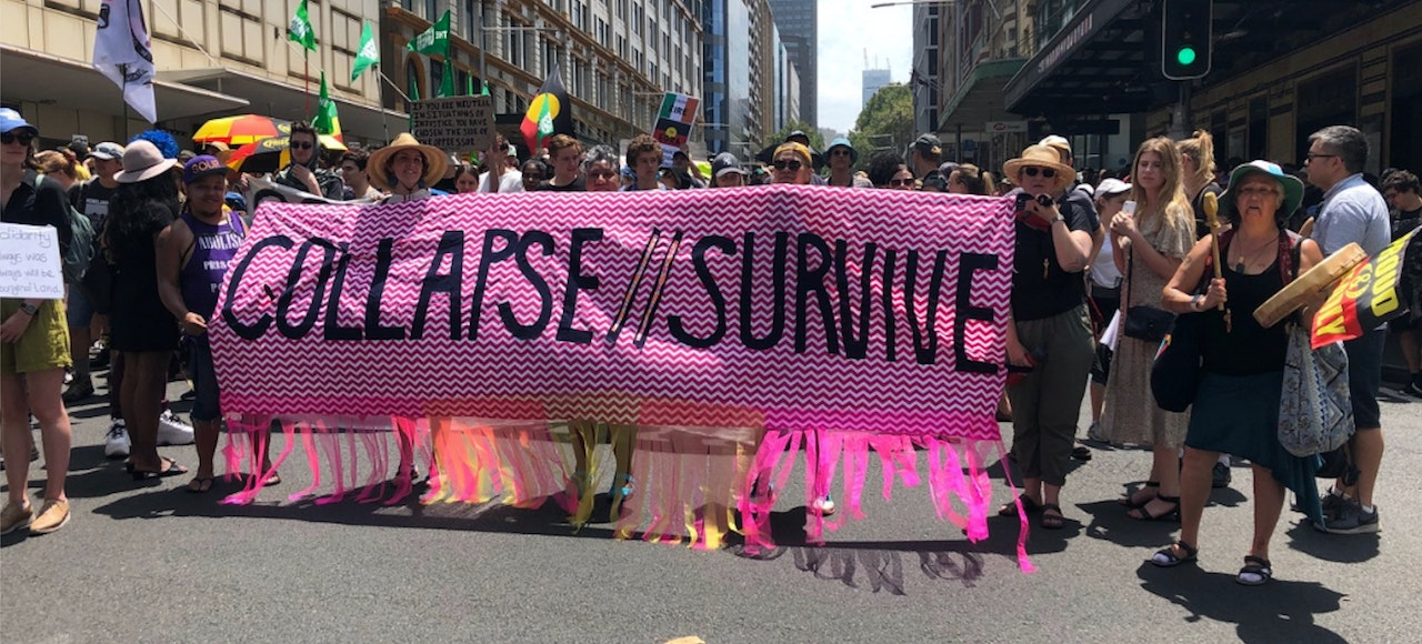 "Crowd of people, men and women on a city street.  Standing behind a pink banner with black text saying ""Collapse//Survive"""